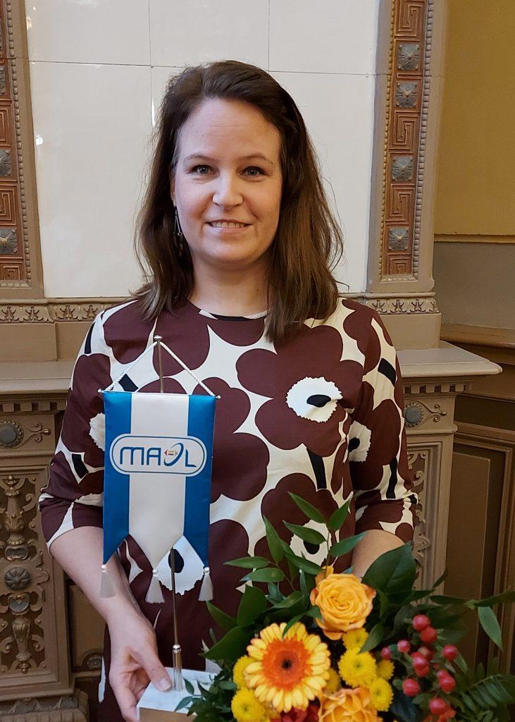 Valokuva Maarit Savolaisesta MAOLin standaarin ja keltaisen kukkakimpun kera